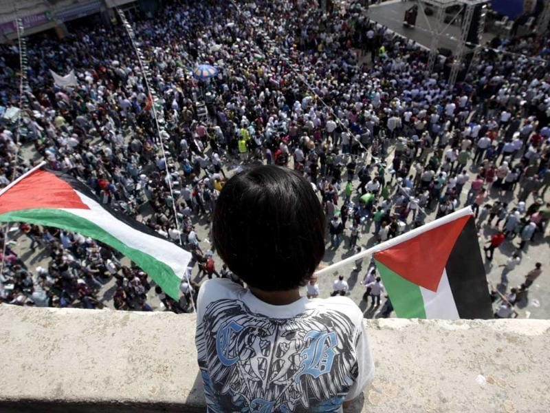 A Palestinian boy holds a flag as he watches a rally in the West Bank city of Ramallah in support of Palestinian President Mahmoud Abbas' bid for statehood recognition in the United Nations.