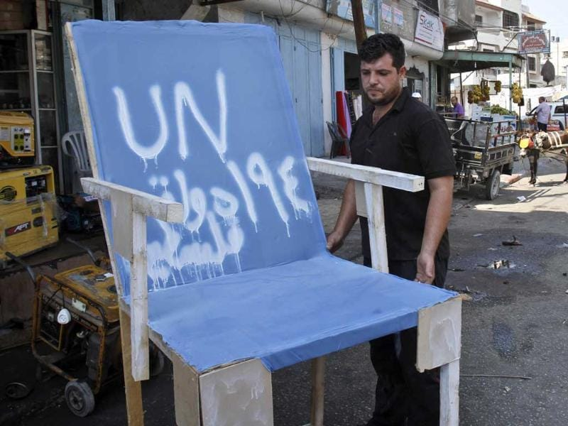 Palestinian carpenter Mustafa Masoud, 24, takes a chair symbolizing the Palestinian statehood bid from his house to be placed in front of the UN offices in Gaza city. Writing in Arabic reads
