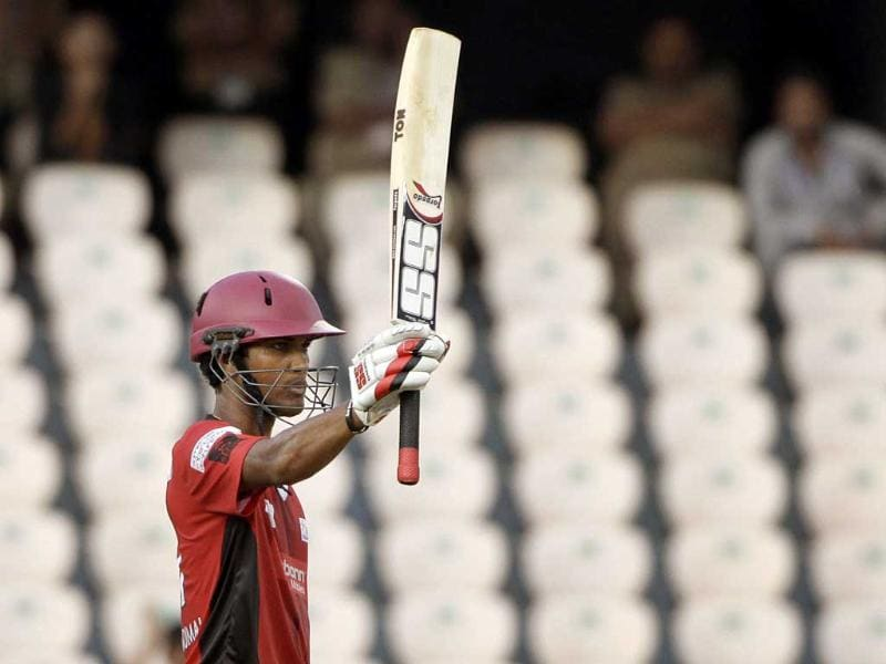 Ruhuna's cricket player Dinesh Chandimal raises his bat to celebrate scoring fifty runs during the Champion League Twenty20 qualifying cricket match between Ruhuna and Leicestershire in Hyderabad.