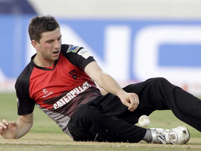 Leicestershire bowler Harry Gurney tries to stop the ball during the Champion League Twenty20 qualifying match between Ruhunu Eleven and Leicestershire in Hyderabad.