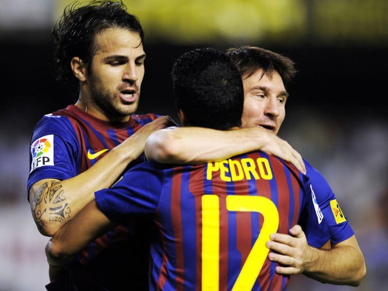 Barcelona's forward Pedro Rodriguez (C) celebrates with teammates Barcelona's forward Cesc Fabregas (L) and Barcelona's Argentinian forward Lionel Messi after scoring a goal against Valencia during their Spanish League football match in Valencia.