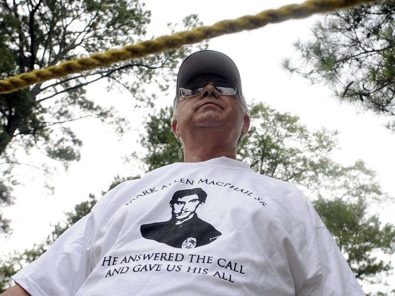 James McMenamin, wearing a T-shirt in support of murdered police officer Mark MacPhail, stands in a separate protest area at the Georgia Diagnostic and Classification prison where convicted killer Troy Davis is set to be executed by lethal injection in Jackson, Georgia September 21, 2011.