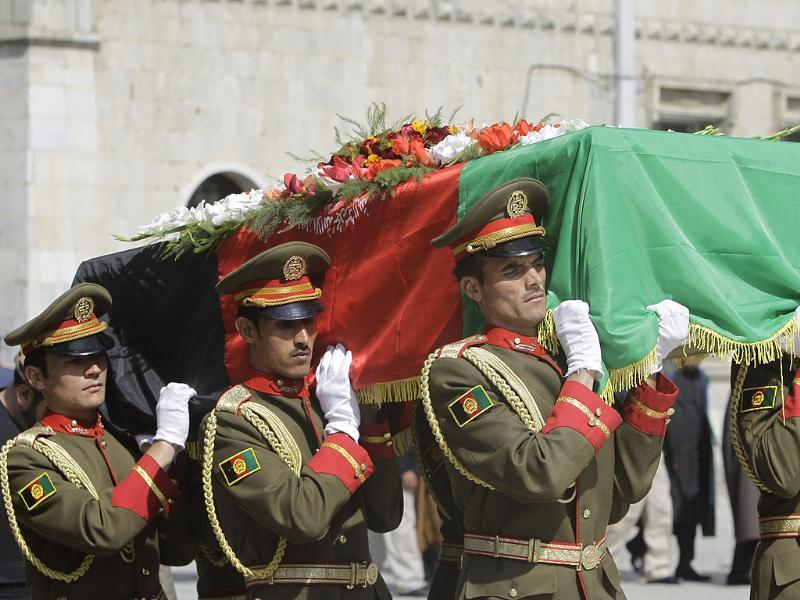 The coffin of Afghan former president Burhanuddin Rabbani who was killed three days ago, is carried by a guard of honor at the presidential palace in Kabul, Afghanistan.