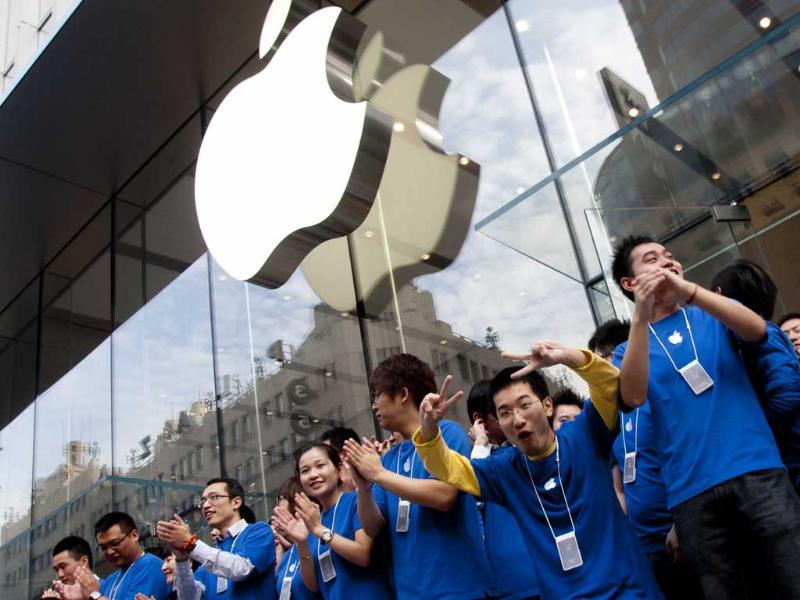 Staff gesture during the opening ceremony of a new Apple store in Shanghai.