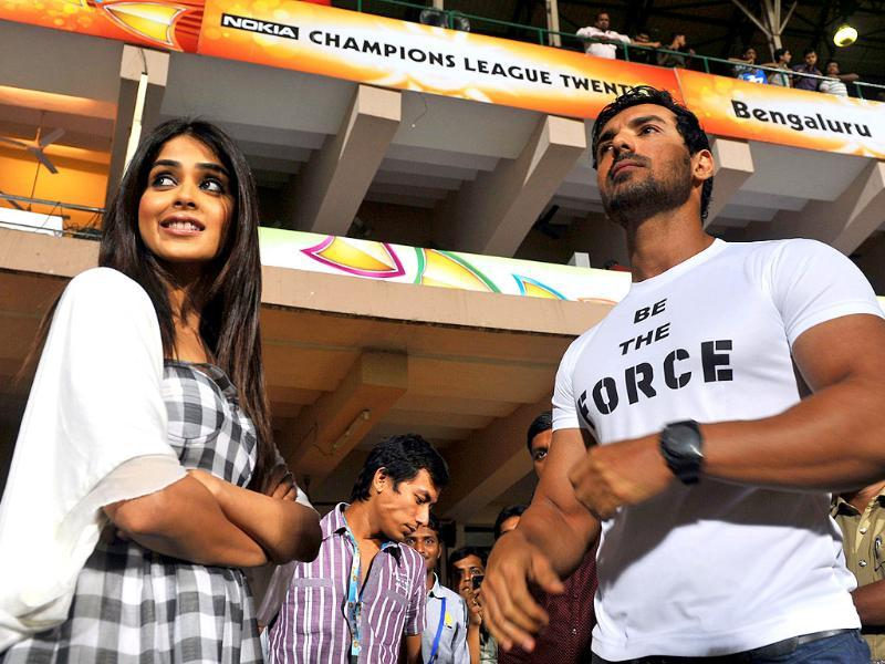 Bollywood actor John Abraham (R) and Genelia at Champions League T20 match between Royal Challengers Bangalore and Warriors at the M Chinnaswamy Stadium in Bangalore.