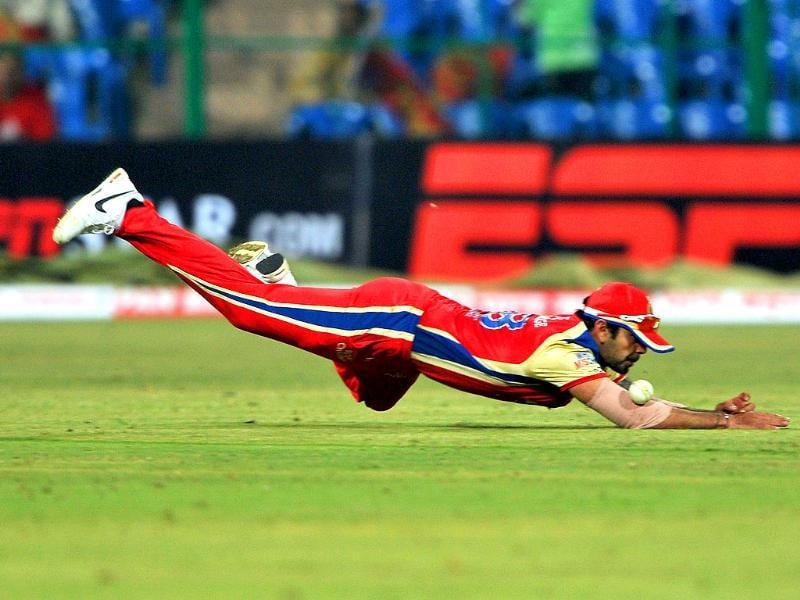 RCB player Virat Kholi dives to stop a shot during the Champions League Twenty20 League group B match between Royal Challengers Bangalore and Warriors at the M Chinnaswamy Stadium in Bangalore.