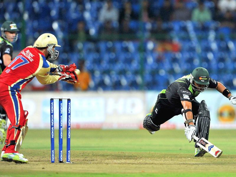 Warriors' batsman Ashwell Prince completes a run while RCB wicket keeper AB de Villiers collects the ball during the Champions League Twenty20 match.