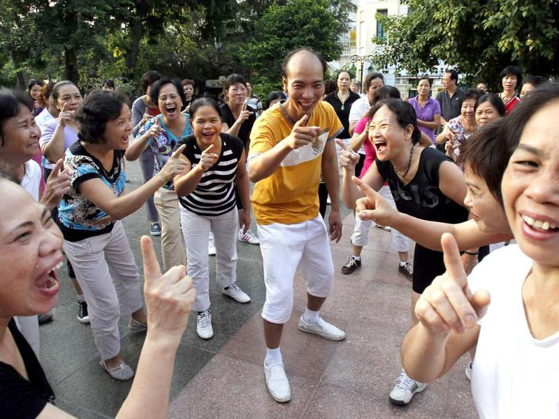 Yoga master Le Anh Son (C) and members of the Laughter Yoga club practise laughing during morning exercise at a public park in Hanoi.