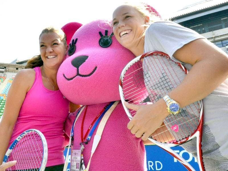 World number one Caroline Wozniacki (R) of Denmark and Agnieszka Radwanska (L) of Poland smile with Sony's Internet mascot Momo after a kids tennis clinic at the Pan Pacific Open tennis tournament in Tokyo.
