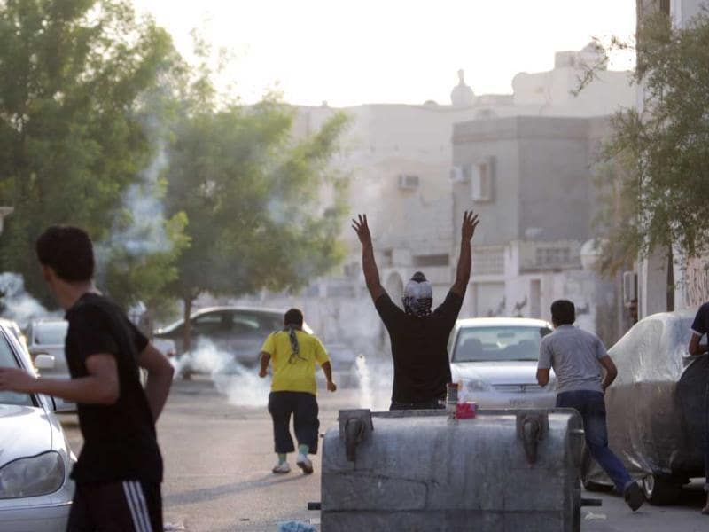 Anti-government protesters clash with riot police firing tear gas in Jidhafs, Bahrain. Bahrain's Sunni rulers are practicing