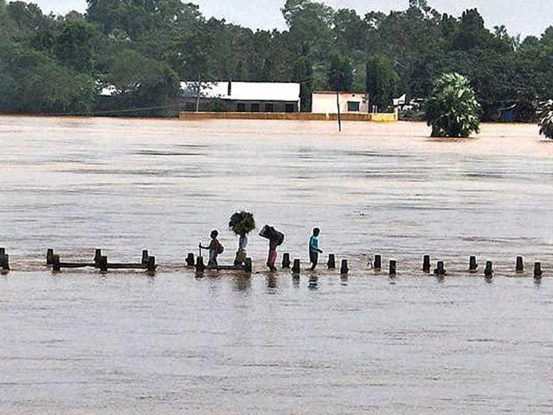 Villagers wade through overflowing flood water on a fly over of Baitarani river at Katarpur village, Jajpur district in Orissa.