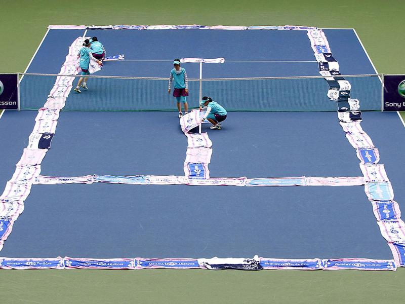 Towels are placed on the wet tennis court as rain falls during a match between Anastasia Rodionova of Australia and Ana Ivanovic of Serbia at the Pan Pacific Open tennis tournament in Tokyo.