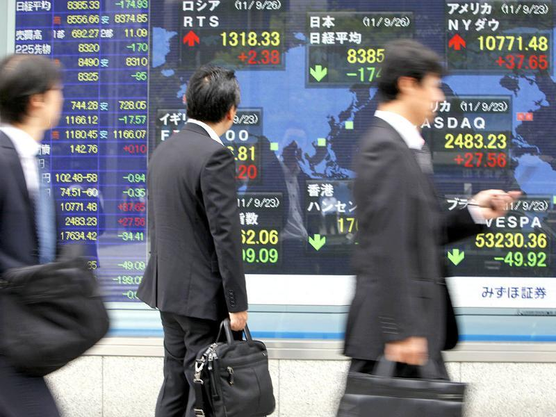 People walk by an electronic stock board of a securities firm in Tokyo.