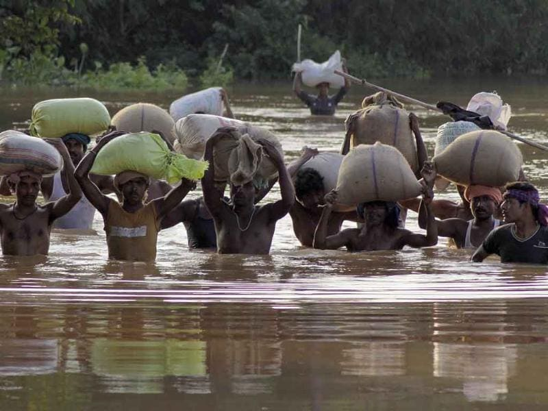 Villagers carry relief materials through flood waters at Rasulpur village in Orissa's Jajpur district. Monsoon rains have left hundreds of thousands of people marooned by the raging waters.