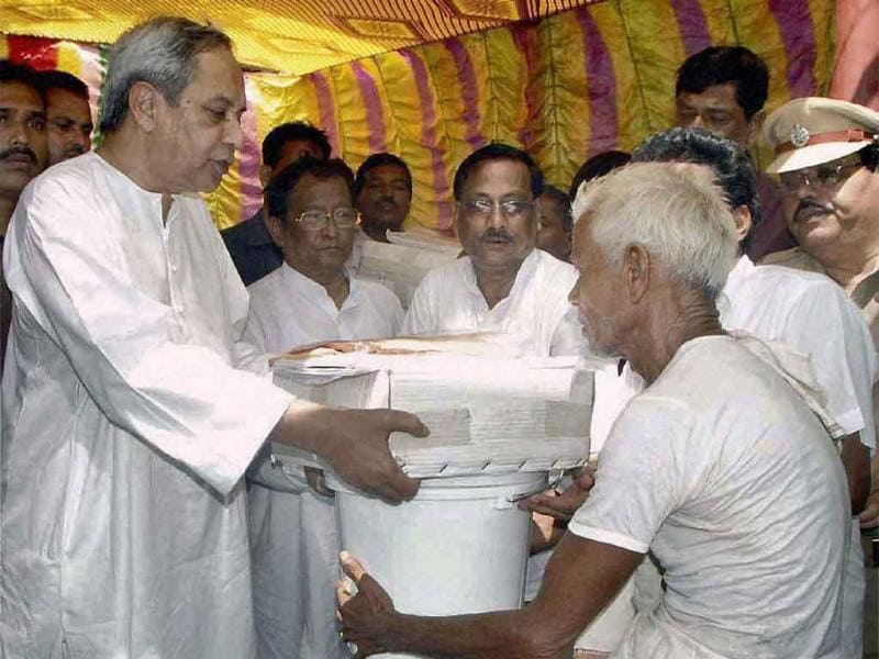 Orissa chief minister Naveen Patnaik distributes relief materials to a flood hit villager at Bilipada village of Banki in Cuttack.