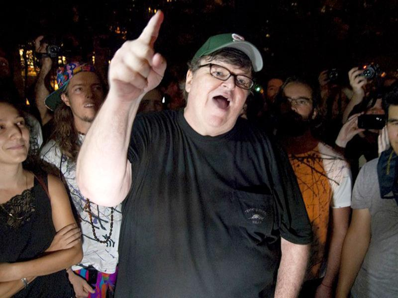 Filmmaker Michael Moore gestures during a visit to the Occupy Wall Street protest in Zuccotti Park in New York. Protesters are camping out in the lower Manhattan plaza to speak out against corporate greed and social inequality.