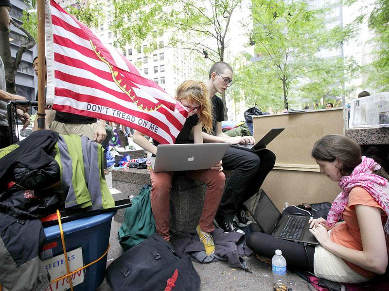 A woman, center, who gave her name as Ketchup, works on a laptop to support the web-based publicity for Occupy Wall Street in Zuccotti Park.