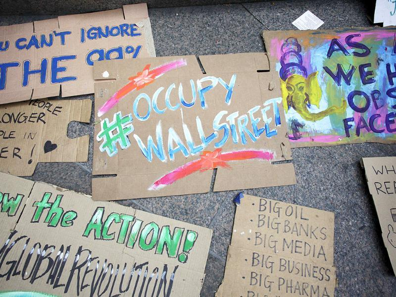 A group of signs is displayed on the sidewalk for use by the protest movement in Zuccotti Park.