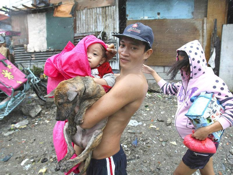A family evacuates to safety with their pet dog at the height of typhoon Nesat Tuesday in Manila, Philippines.