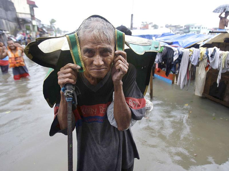 An old Filipino man living beside a river evacuates his flooded home in Navotas, north of Manila, Philippines as Typhoon Nesat hits the country.
