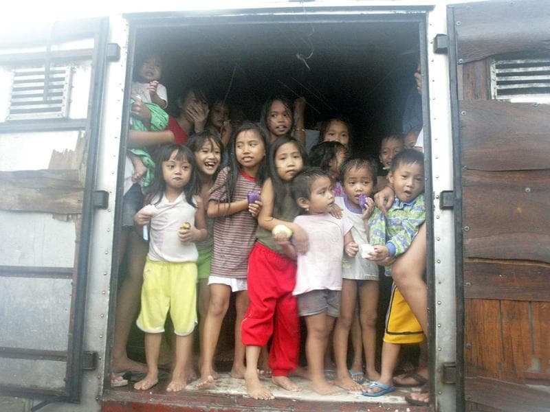 Children look out from the back of a delivery truck as they evacuate their shanties after floodwaters brought by Typhoon Nesat, locally known as Pedring, hit Baseco, Tondo city, in metro Manila.
