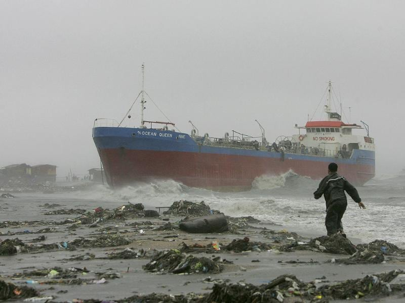 A resident approaches an oil tanker after it broke off its anchor and slammed a row of shanties as typhoon Nesat hit Philippines.