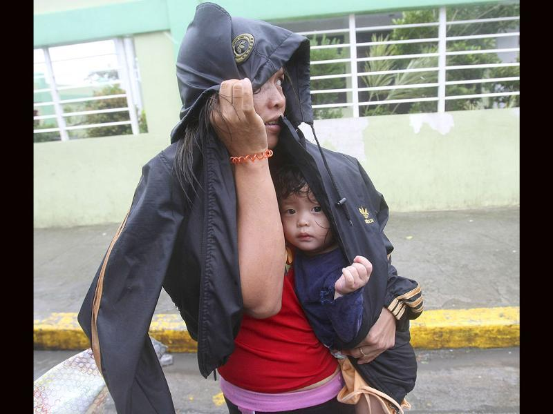 A mother flees her home with her baby to evacuate to safer grounds at the height of typhoon Nesat in Manila, Philippines.