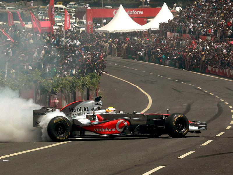 Lewis Hamilton, the controversial Mclaren Mercedes driver woos the crowd in the award winning MP4-23 car during the Formula One car run at Nice road in Bangalore.