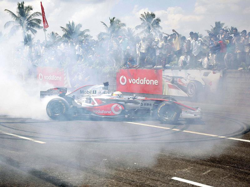 McLaren driver Lewis Hamilton of Britain performs on the Bangalore-Mysore highway during a promotional event ahead of the India Formula One Grand Prix, on the outskirts of Bangalore.