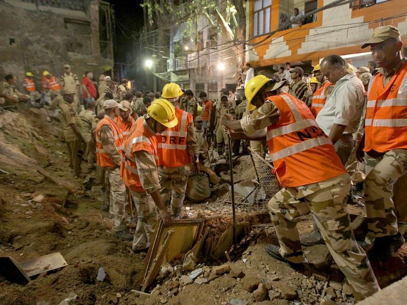 Rescue workers remove the debris as they look for survivors after a building collapsed in New Delhi.