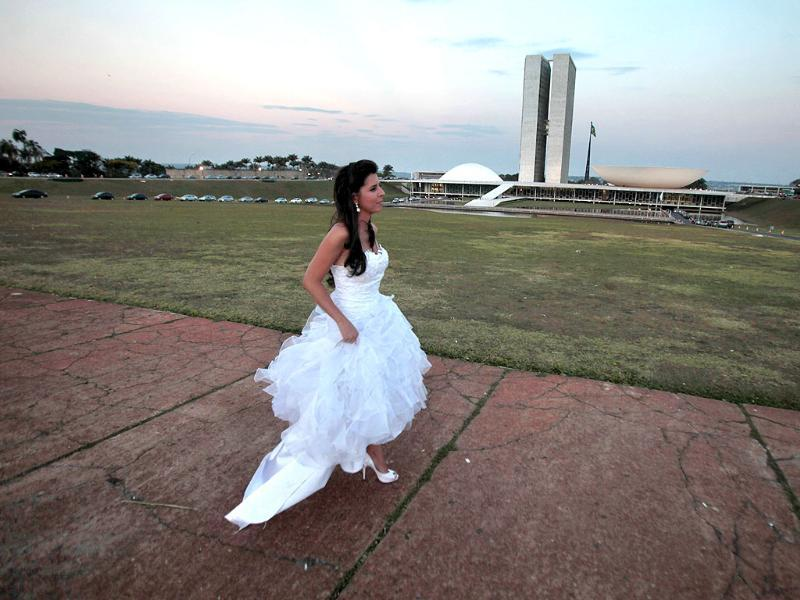 A bride walks to her car after a photo shoot in her wedding gown outside the National Congress in Brasilia, Brazil.