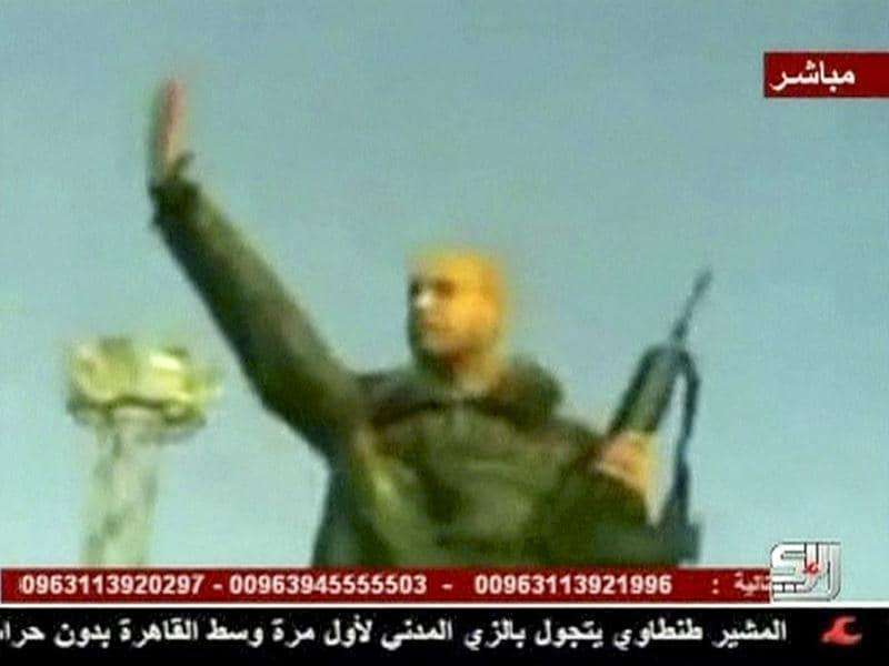 A still image from video broadcast by a Syria-based television station shows what the station describes as Muammar Gaddafi's son Saif al-Islam holding a rifle as he rallies his forces at an unidentified location in Libya.