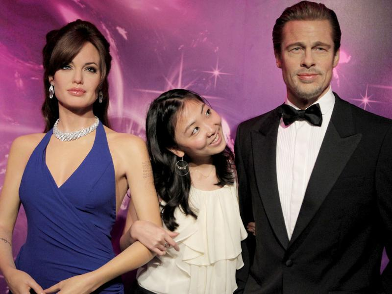A model, center, poses with Brad Pitt and Angelina Jolie's wax figures at the Madame Tussauds wax exhibition in Tokyo.