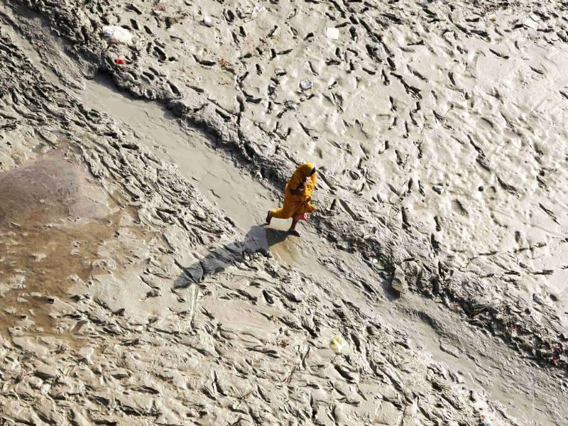 A woman walks on the muddy banks of the Ganges river before taking a holy dip during the Navratri festival, in Allahabad.