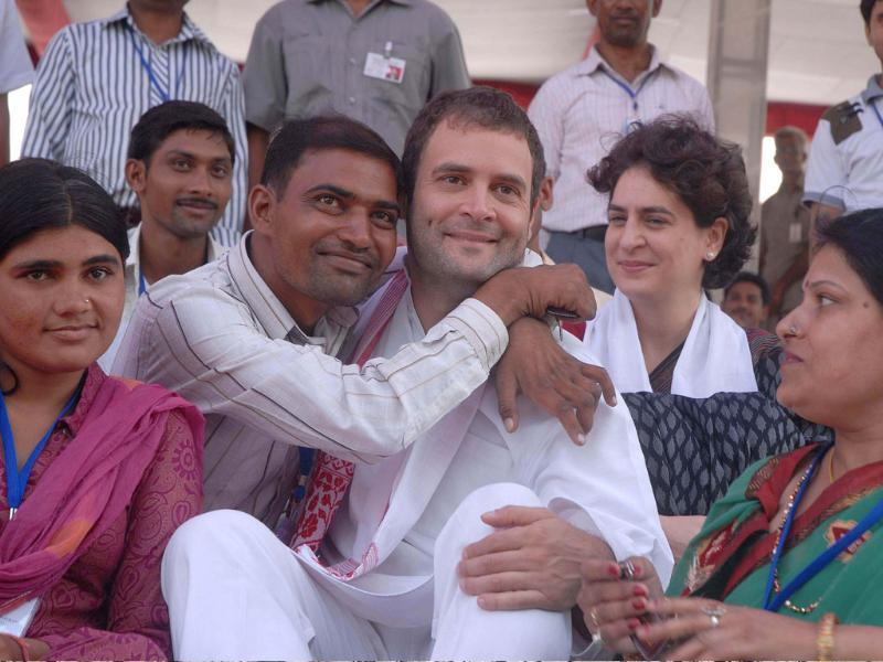 A physically disabled person hugs Congress general secretary Rahul Gandhi as he distributes motorised tri-wheelers in New Delhi; sister Priyanka looks on.