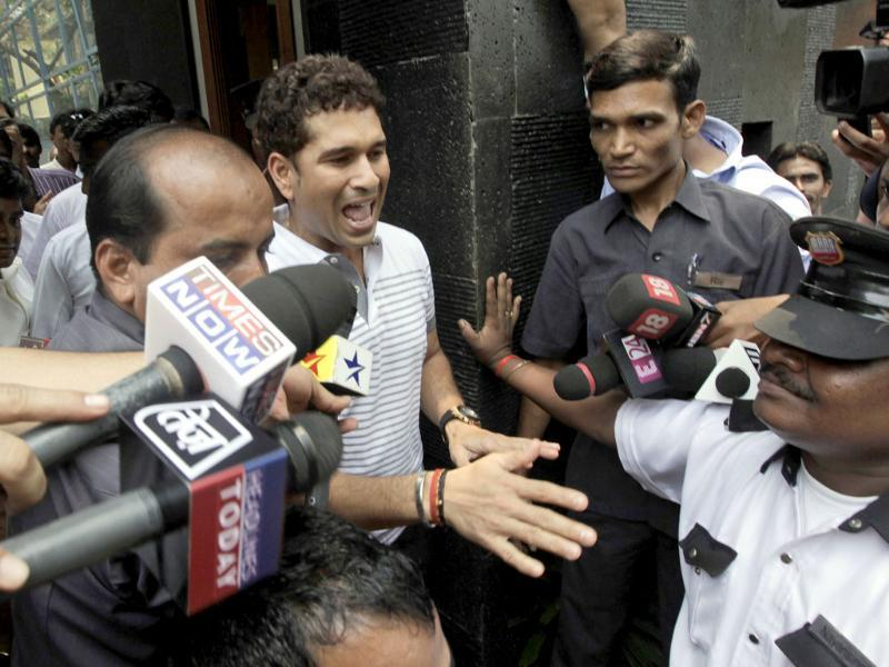 Sachin Tendulkar reacts as he interacts with school children who arrived to greet him after he moved to his new house in Bandra area in Mumbai.