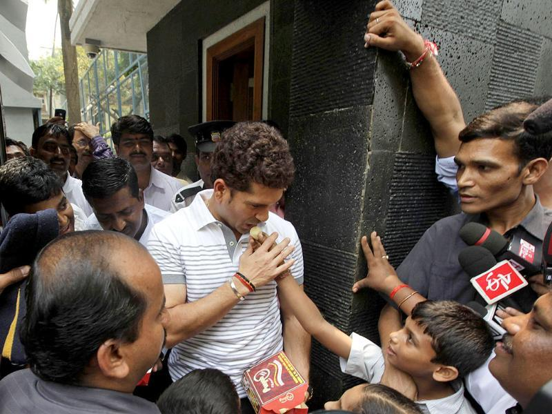 Sachin Tendulkar, center, receives sweets from school children who arrived to greet him after he moved to his new house in Bandra area in Mumbai.