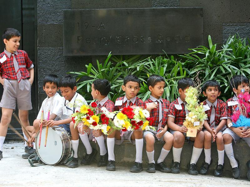 School children wait in front of Sachin Tendulkar's new house at Perry Cross Road in Bandra, Mumbai.