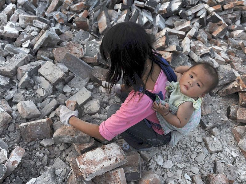 A migrant worker collects bricks as she carries her child on her back, at a demolition site in Jiaxing, Zhejiang province. China's housing inflation eased a touch in August with home prices in major big cities remaining flat for a second consecutive month, official data showed.