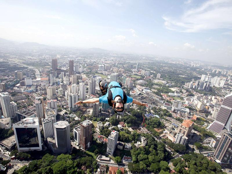 BASE jumper Sammy Rohan from Sydney leaps with a parachute off Kuala Lumpur Tower.