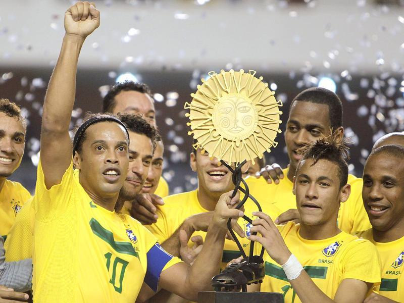 Brazil's players Ronaldinho and Neymar hold the trophy as they celebrate with teammates after defeating Argentina 2-0 in a soccer friendly match in Belem, Brazil.