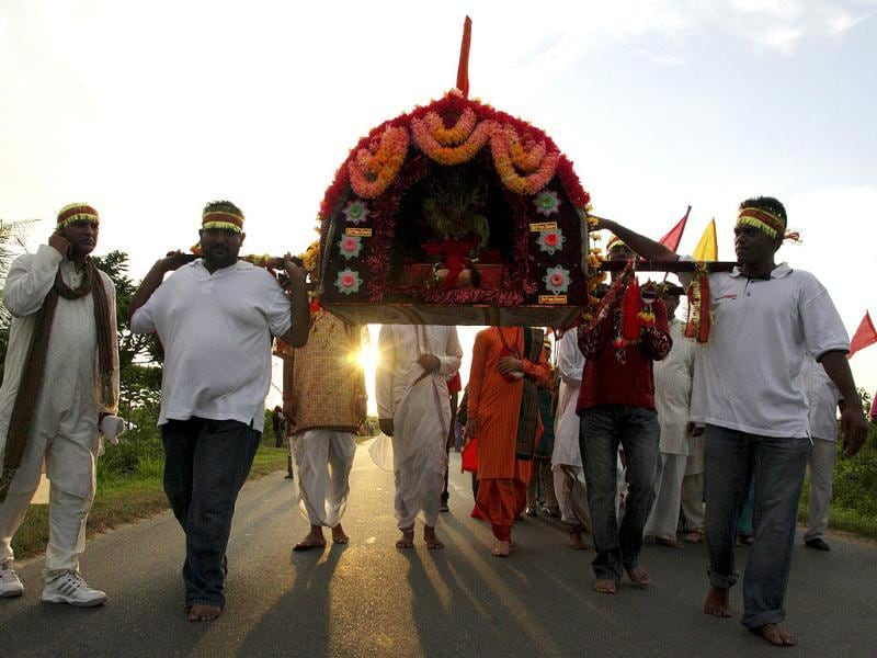Surinamese Hindu devotees carry a statue of the Hindu Goddess Durga while participating in Jalyatra, a procession in which they carry a clay water jar with a dried coconut to symbolize the earth and its blessings on the eve of the Navratri festival of nine nights.