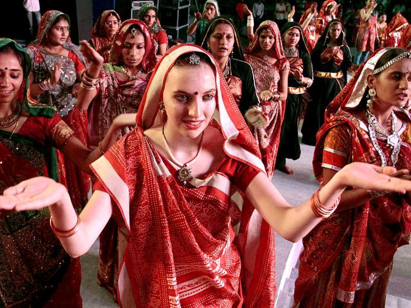 An Italian participant, center in traditional Indian attire performs with others in a rehearsal for Navratri festival celebrations in Ahmadabad.