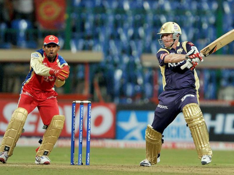 Wicket keeper of Royal Challengers Bangalore T. Dilshan (left) watches as Brad Haddin of Kolkata Knight Riders scores a boundary during the Champions League Twenty20 League match at the M. Chinnaswamy Stadium in Bangalore.