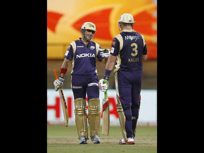 Kolkata Knight Riders captain Gautam Gambhir, left, greets teammate Jacques Kallis on scoring a half century during their Champions League Twenty20 cricket match against Royal Challengers Bangalore in Bangalore.