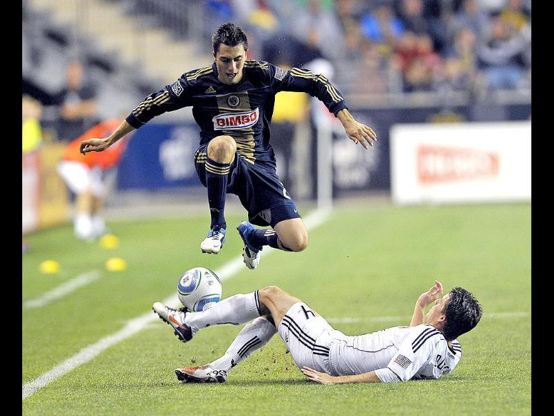 Philadelphia Union's Michael Farfan, left, jumps over DC United's Marc Burch (4) during the second half of an MLS soccer match in Chester. The Union won, 3-2.