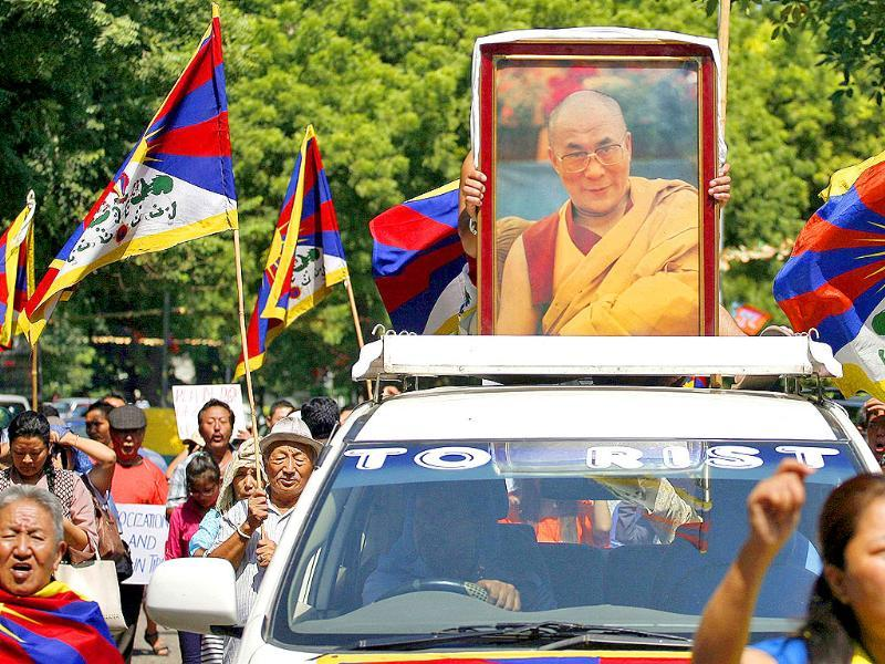 A Tibetan exile holds a portrait of Tibet's exiled spiritual leader the Dalai Lama atop a car during a protest in New Delhi.