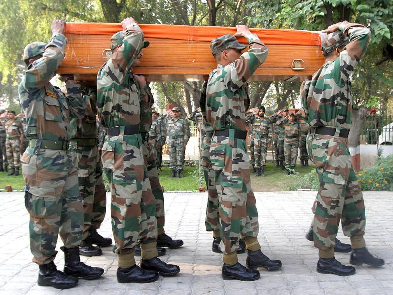 Army soldiers carry a coffin containing the body of soldier Ravi Kumar during a wreath laying ceremony at an army base in Srinagar.
