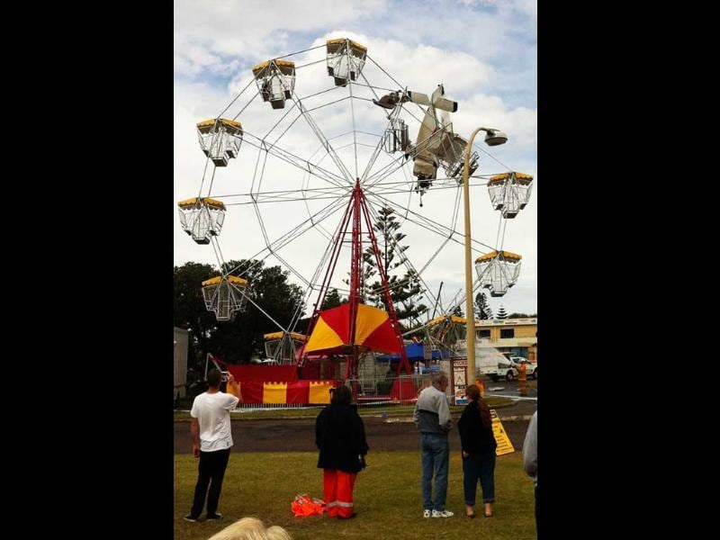 People look at an ultra-light Cheetah S200 airplane stuck in a ferris wheel after it crashed into the fairground attraction following takeoff from a nearby airstrip in Taree, New South Wales.