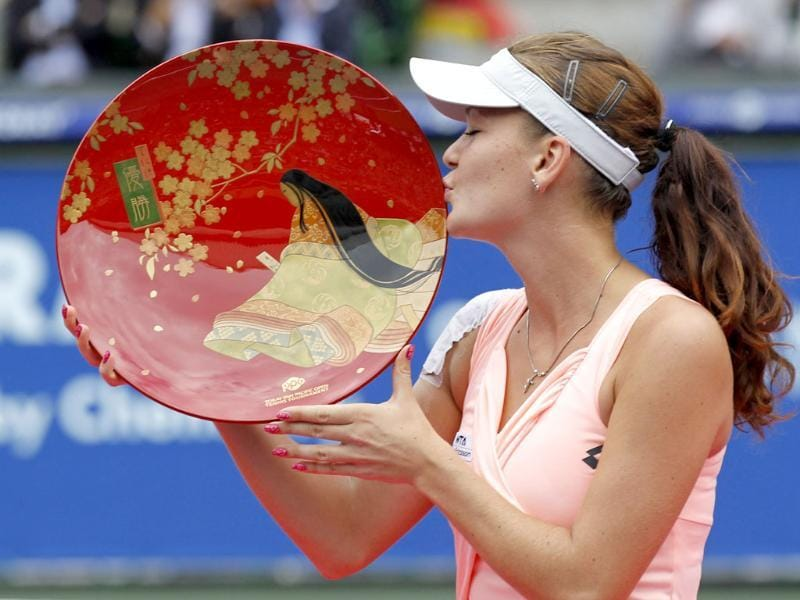 Poland's Agnieszka Radwanska kisses her victory trophy after defeating Russia's Vera Zvonareva in their final match of the Pan Pacific Open tennis tournament in Tokyo.